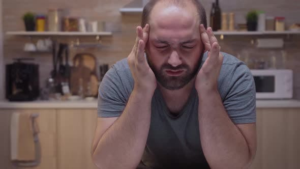Thumbnail for Man with Headaches Sitting in the Kitchen