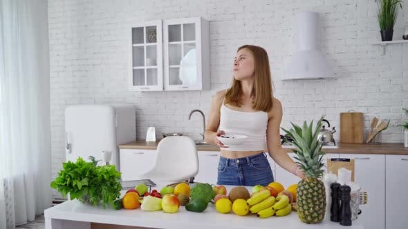 Pretty woman in the modern kitchen. Organic fruit and vegetables on the table.