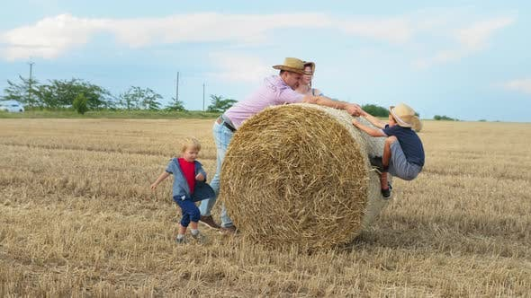 Family in Nature, Parents Help Little Boy To Ride on Bale of Hay