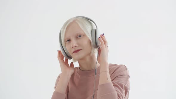 Thumbnail for Young Albino Girl in the White Earphones Listening To Music. Girl Albino Casting in a Music Studio