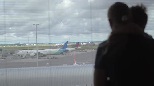Back View of Mother and Son Standing and Watching in the Window on the Airplane Runway, Amsterdam