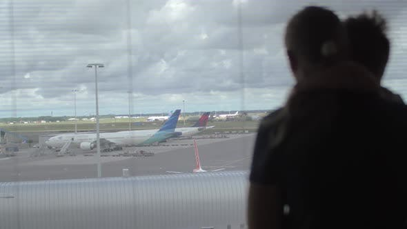 Thumbnail for Back View of Mother and Son Standing and Watching in the Window on the Airplane Runway, Amsterdam