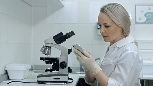 Thumbnail for Scientist working with microscopes and smartphone in chemical lab