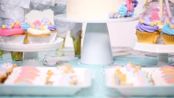 Unicorn cake with buttercream on the party table at little girl's birthday party.