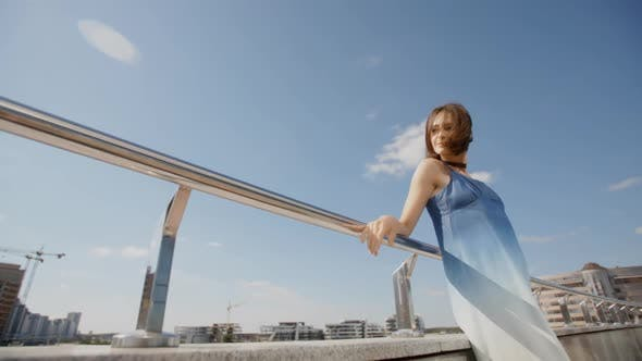Cover Image for Young Woman In Long Blue Dress Posing In The City Street