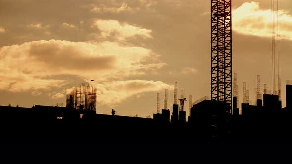 Cover Image for Silhouette of Construction Workers and Tower Crane Working on Construction Site, Constructors Work