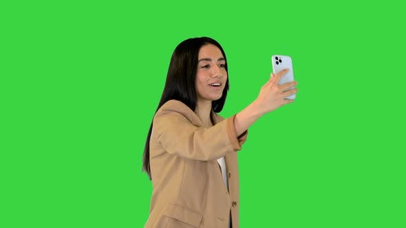 Young Indian Girl Walking and Making a Video Call on a Green Screen Chroma Key