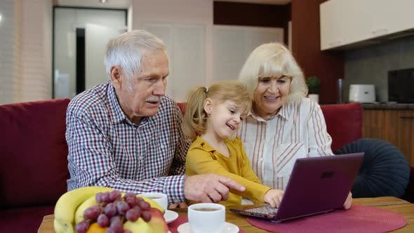Grandfather and Grandmother Sitting in Living Room and Teaching Small Granddaughter Using Laptop