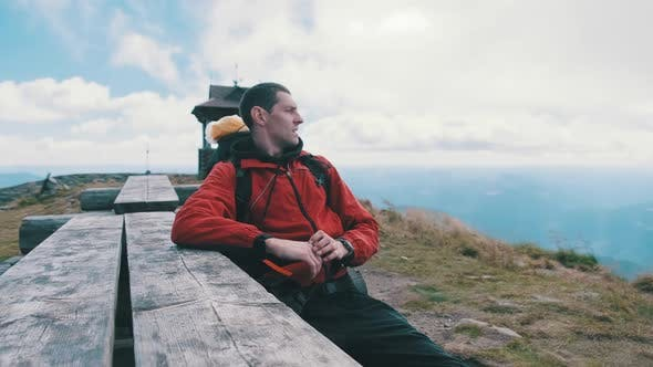 Thumbnail for Tourist with Backpack on Top of Mountain Sat Down To Rest at an Old Wooden Table