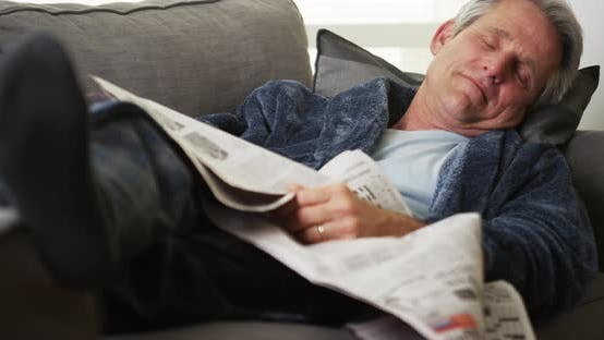 Senior man sleeping newspaper