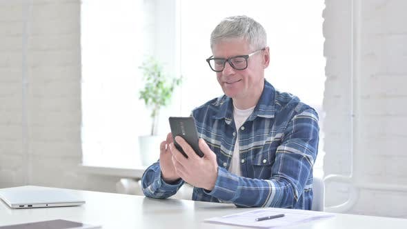 Thumbnail for Cheerful Casual Middle Aged Man Using Smartphone in Office