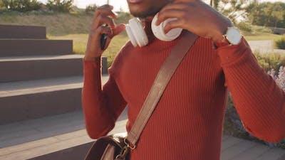 Black Man Listening to Music in Headphones Outdoors