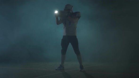 American Football Sportsman Player in Football Helmet Standing on the Field