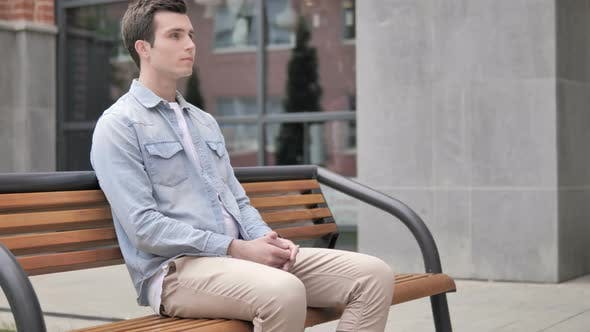 Thumbnail for Serious Casual Young Man Sitting Outdoor