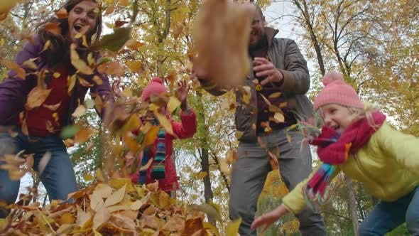 Thumbnail for Family Throwing Yellow Leaves in Air