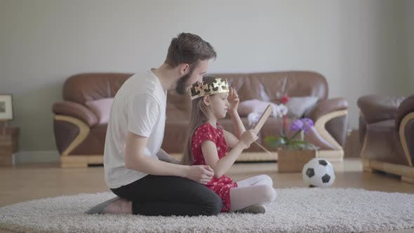 Thumbnail for Portrait Young Handsome Father Dressed His Cute Little Long-haired Daughter's Head with Crown and