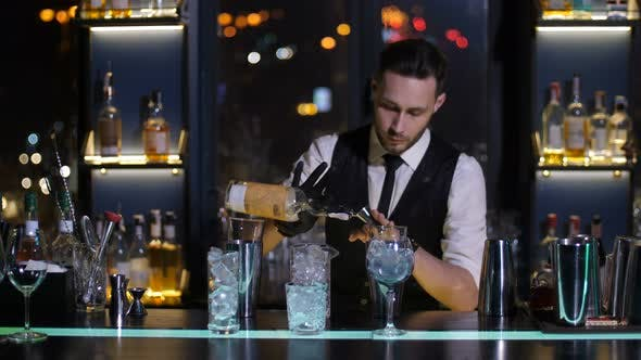 Barman Pouring Liquor From Bottle in Jigger at Bar