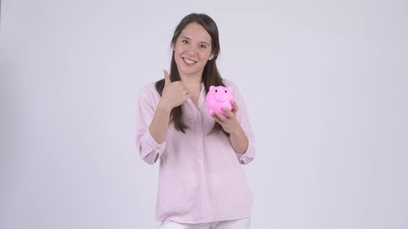 Young Happy Multiethnic Businesswoman Holding Piggy Bank and Giving Thumbs Up
