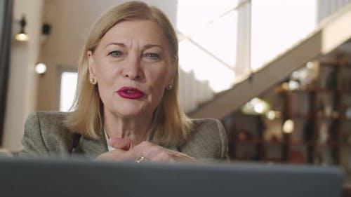 Senior Businesswoman Web Calling on Laptop in Restaurant