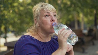 Fat Woman Drinking Water at the Street
