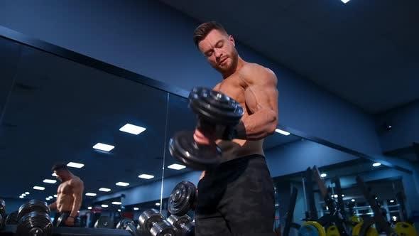 Hübscher Bodybuilder trainiert mit Hanteln im modernen Fitnessstudio. Zeitlupe