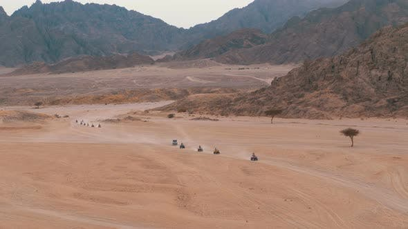 Thumbnail for Column of a Quad Bike Rides Through the Desert in Egypt on Backdrop of Mountains. Driving ATVs.