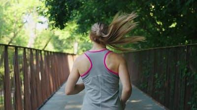 Woman Jogging on Bridge in Slow Motion
