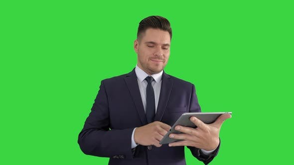 Thumbnail for Handsome Man Swiping Pages on Tablet and Smiling To Camera on a Green Screen, Chroma Key