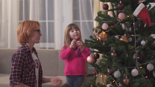 Thumbnail for Cute Little Girl Helps Her Mother Decorate the Christmas Tree with Toys. Relationship Mothers
