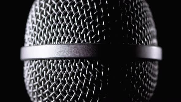 Cover Image for The Microphone Rotates on a Black Background. Dynamic Microphone Grid Spins Close-up