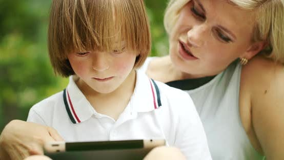 Thumbnail for Down Syndrome Boy Scrolling Tablet with Mother