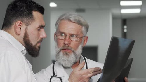 Senior Male Doctor and His Colleague Discussing Xray Scans of a Patient