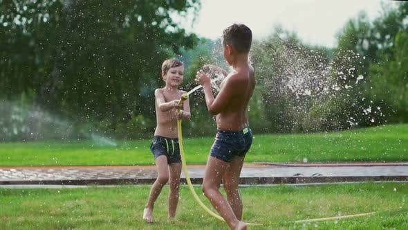 Thumbnail for Children Play in Summer with Water Pouring From a Hose