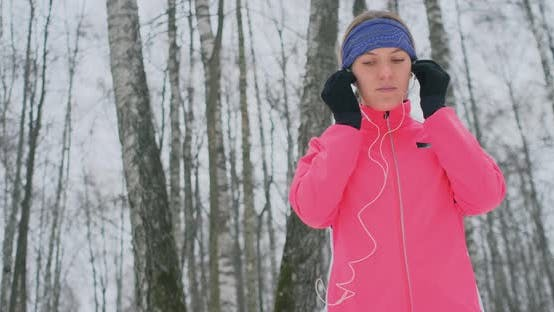 Thumbnail for A Young Girl on the Morning Jog Holds in Her Hands a Smartphone Picks a Music Track for Training