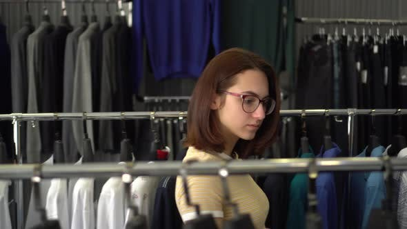 Young Woman Chooses Clothes in the Store. Clothing Store.