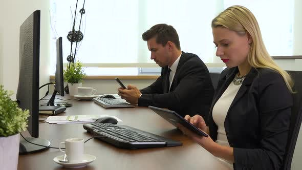 Thumbnail for Two Office Workers, Man and Woman, Work on A Tablet and A Smartphone