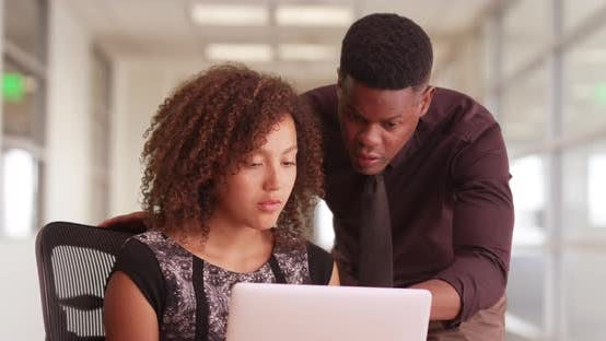 Thumbnail for African American male and female work in office hallway on their laptop