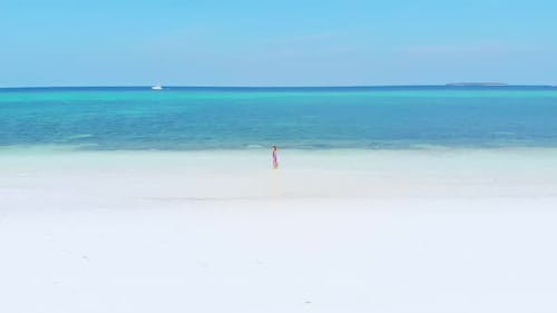 Aerial slow motion: woman walking on white sand tropical beach turquoise water Moluccas Indonesia