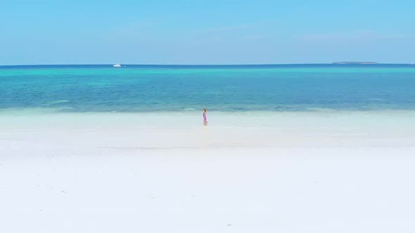 Thumbnail for Aerial slow motion: woman walking on white sand tropical beach turquoise water Moluccas Indonesia