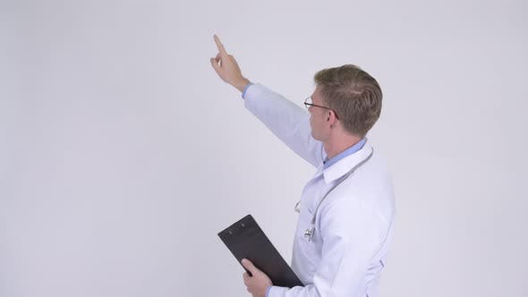 Thumbnail for Rear View of Young Man Doctor Thinking and Pointing Finger