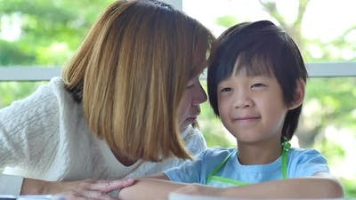 Asian Mother Whispers Something To Her Son