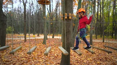 Little girl in orange helmet and protective gear on rope-way in autumn  forest. rope park.