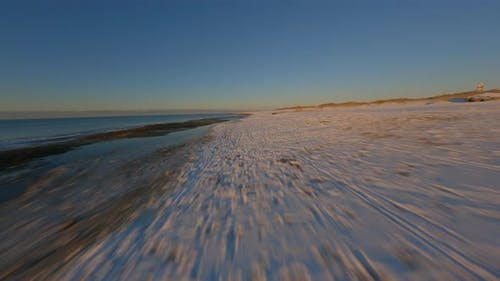 Aerial Drone FPV Hovering Above Sea Shore Filled with Snowy Patches By Beach