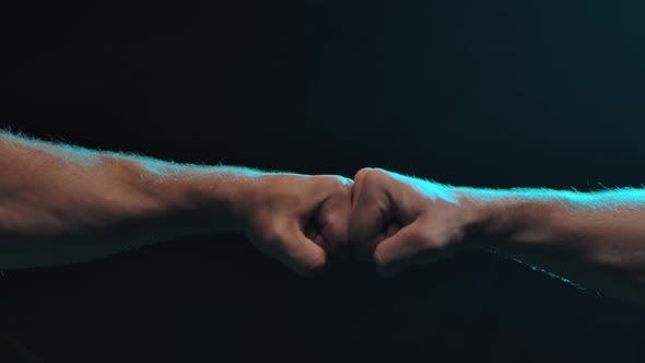 Thumbnail for Conflict Concept. The Clash of Two Fists of Male Athletes on a Black Background. Slow Motion