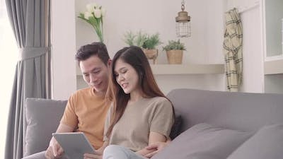 Asian couple using tablet for online shopping in internet in living room at home at home