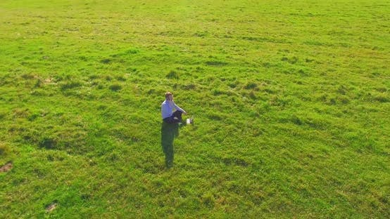 Thumbnail for Low Orbital Flight Around Man on Green Grass with Notebook Pad at Yellow Rural Field.