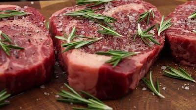 Raw seasoned ribeye beef steaks