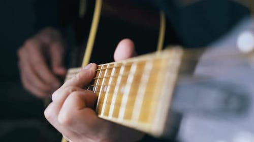 Skilled Guitarist Strikes Various Chords on Acoustic Guitar