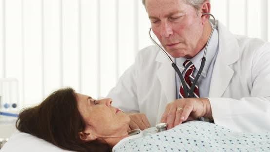 Senior doctor listening to mature patient's heart