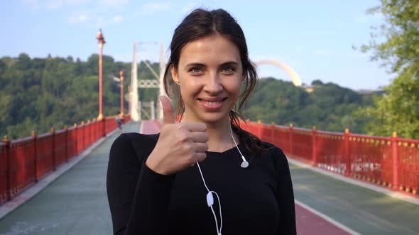 Thumbnail for Attractive Brunette Woman Shows Thumb Up and Smiles. Portrait of Happy Adult Female on the Bridge